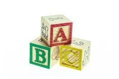 Cierre encima de los bloques coloridos del alfabeto de ABC aislados en blanco Foto de archivo libre de regalías