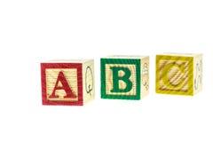 Cierre encima de los bloques coloridos del alfabeto de ABC aislados en blanco Fotografía de archivo