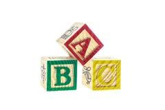 Cierre encima de los bloques coloridos del alfabeto de ABC aislados en blanco Imagen de archivo libre de regalías