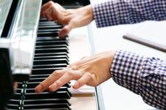 Cierre encima de los hombres jovenes que juegan en piano fotos de archivo libres de regalías