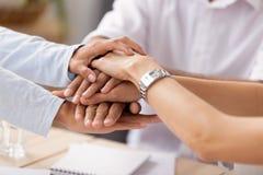 Cierre encima de los hombres de negocios diversos de la visi?n que ponen las manos apiladas juntas imagen de archivo