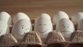 Cierre encima de los huevos del pollo con las caras pintadas en una caja de cart?n El concepto de Pascua almacen de metraje de vídeo