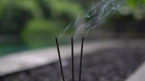 Cierre encima de los palillos ardientes del incienso afuera como símbolo del apaciguamiento y de la relajación metrajes