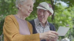 Cierre encima de los pares adultos adorables del retrato que miran las fotos viejas que recuerdan momentos felices sentarse en un almacen de metraje de vídeo