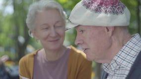 Cierre encima de los pares adultos lindos del retrato que miran las fotos viejas que recuerdan momentos felices sentarse en un ba metrajes