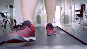 Cierre encima de los pies musculares de las piernas de los hombres de los zapatos que corren en entrenamiento de la rueda de ardi almacen de video