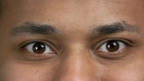 Cierre encima de ojos marrones del hombre de piel morena almacen de video