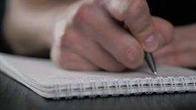 Cierre encima de tiro macro estupendo de una escritura de la mano del hombre algo en el lápiz de papel del cuaderno almacen de video