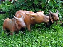 Cierre encima del búfalo y situación cocida vaca de la muñeca de la arcilla en campo de hierba verde en medio del arbusto enorme  fotografía de archivo