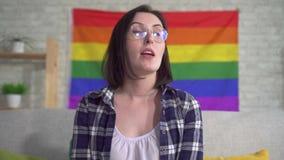 Cierre encima del blogger bonito joven de la mujer en la camisa en el fondo de la bandera del vídeo de los expedientes de LGBT almacen de metraje de vídeo