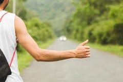Cierre encima del brazo joven y de la mano que hacen autostop en el camino de la montaña imágenes de archivo libres de regalías