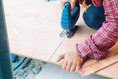 Cierre encima del carpintero asiático del hombre que usa las sierras eléctricas para cortar el tablero grande de madera en un emp foto de archivo