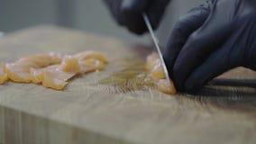 Cierre encima del cocinero de f en los guantes de goma negros que cortan salmones en el tablero de madera en primer moderno del r almacen de video