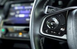 Cierre encima del control de travesía del coche en el volante del coche con a borrosa fotografía de archivo