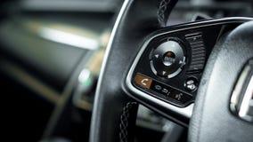 Cierre encima del control de travesía del coche en el volante del coche con c borrosa imágenes de archivo libres de regalías