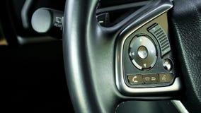 Cierre encima del control de travesía del coche en el volante del coche con c borrosa foto de archivo libre de regalías