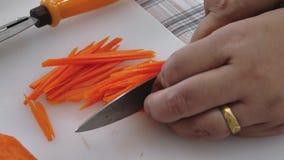 Cierre encima del corte de la mano y cortar un pice de la zanahoria almacen de video