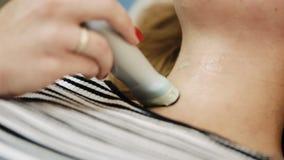 Cierre encima del diagnóstico de la tiroides en centro médico Mujer joven que hace el examen del ultrasonido del cuello en el hos almacen de video
