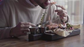 Cierre encima del hombre eatting el plato delicioso impresionante con la carne asada a la parrilla y las verduras que se sientan  metrajes