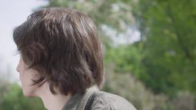 Cierre encima del hombre joven nervioso solo del retrato que se sienta en el banco en el parque que espera su amigo o novia E almacen de metraje de vídeo