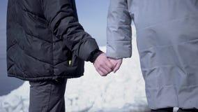 Cierre encima del hombre que camina con una mujer que lleva a cabo las manos Vista que sorprende de un norte o de South Pole nevo metrajes