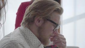 Cierre encima del hombre rubio acertado del retrato en los vidrios que se sientan en una oficina cómoda ligera con netbook en la  almacen de video