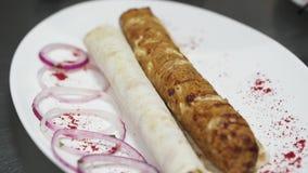 Cierre encima del kebab fresco sabroso que asperja con paprika en la placa grande con la cebolla y la pita violetas Porción de la almacen de metraje de vídeo
