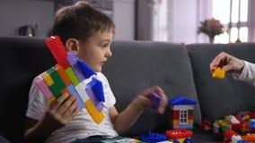 Cierre encima del muchacho lindo que juega con el juguete de bloques almacen de metraje de vídeo
