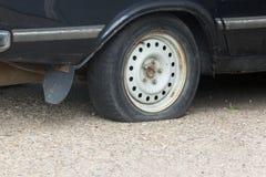 Cierre encima del neumático desinflado y del coche viejo en la reparación que espera del camino para imagen de archivo