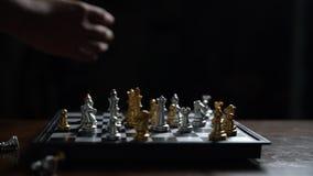 Cierre encima del pedazo de ajedrez del barrido del hombre en el tablero de ajedrez almacen de video