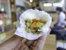 Cierre encima del relleno verde del curry de los bollos cocidos al vapor blancos a disposición en el fondo Blurred foto de archivo