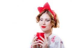 Cierre encima del retrato de la mujer joven hermosa que se divierte que sostiene la taza roja de ojos sonrientes felices de la be Fotos de archivo