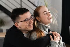 Cierre encima del retrato principal del tiro del hombre joven y de la mujer felices sonrientes que abrazan y que miran lejos Cari foto de archivo