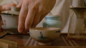 Cierre encima del té chino de colada de la infusión del amo de gaiwan a la jarra de la imparcialidad almacen de video