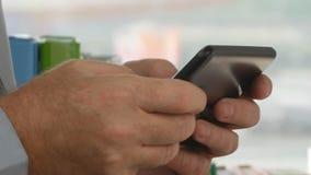 Cierre encima del texto de la mano del hombre de negocios usando la comunicación del teléfono móvil en oficina de la compañía almacen de metraje de vídeo