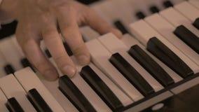 Cierre - encima del tiro de jugar masculino de las manos del sintetizador en el partido metrajes