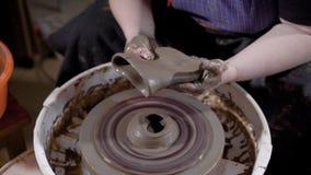 Cierre encima del tiro de las manos de una cerámica femenina que hace el nuevo florero a mano en el taller metrajes