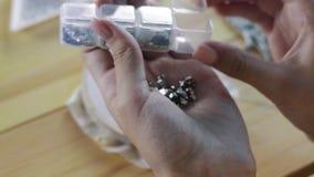 Cierre encima del tiro - diseñador profesional de la joyería que hace la broche hecha a mano con las gotas en el estudio, taller  almacen de metraje de vídeo