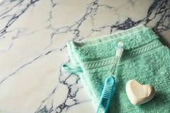 Cierre encima del toallita, del jabón y del cepillo de dientes azules en la placa de mármol foto de archivo libre de regalías