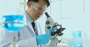 Cierre encima del vídeo de la escena de la muestra de caída del científico de líquido en placa de Petri en el microscopio para su metrajes