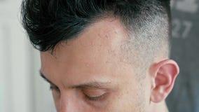 Cierre extremo encima de la cara del hombre en salón de la peluquería El peluquero corta el pelo por las podadoras almacen de video