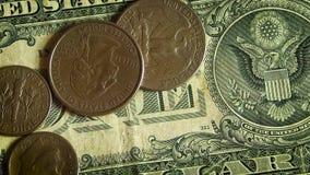 Cierre extremo para arriba de diversas monedas en un billete de dólar almacen de video
