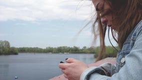 Cierre femenino de la cara encima de la mirada en su smartphone almacen de metraje de vídeo