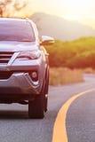 Cierre francamente del nuevo estacionamiento de plata del coche de SUV en la carretera de asfalto Foto de archivo