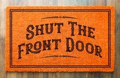 Cierre a Front Door Orange Welcome Mat en el fondo de madera del piso imágenes de archivo libres de regalías