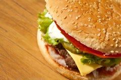 Cierre grande del cheeseburger para arriba en la tabla de madera Fotografía de archivo libre de regalías