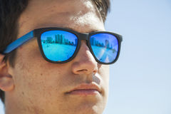 Cierre grande encima del retrato de un muchacho del adolescente que lleva el sol azul del espejo Foto de archivo