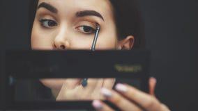 Cierre la cara hermosa de la chica joven para conseguir el maquillaje Mujer que aplica la sombra de ojos en sus cejas con un cepi almacen de metraje de vídeo