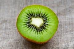 Cierre macro de la fruta de kiwi para arriba en tela del lino de la arpillera Fotos de archivo libres de regalías