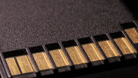 Cierre macro para arriba de la tarjeta de memoria Flash del sd del ordenador que gira alrededor almacen de metraje de vídeo